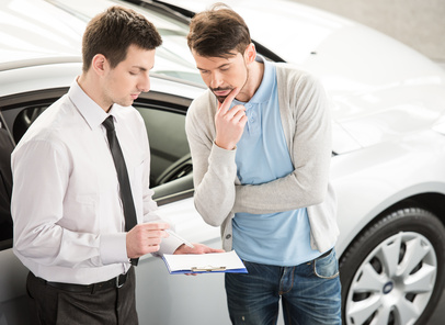 Car salesperson demonstrating a new automobile to young couple.